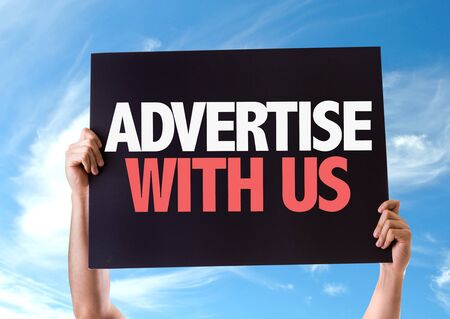advertise with us: Hands holding blackboard with Advertise With Us on sky background Stock Photo