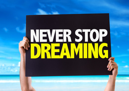 Hands holding blackboard with Never Stop Dreaming on beach background