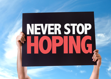 believing: Hands holding card with text Never stop hoping on sky background Stock Photo