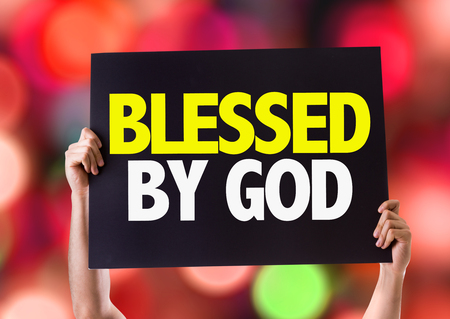 spiritual bless: Hands holding blackboard with Blessed By God on bokeh background Stock Photo
