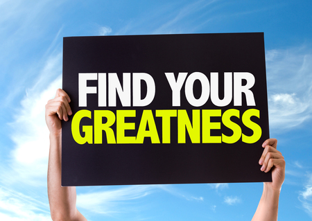 greatness: Hands holding blackboard with Find Your Greatness on sky background