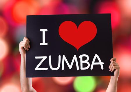 Hands holding blackboard with I Heart Zumba on bokeh background