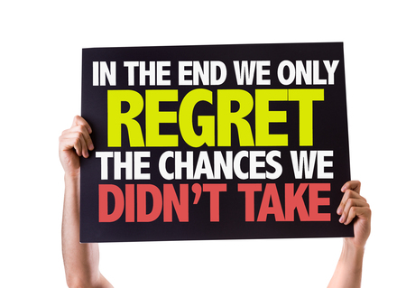 regret: Hands holding blackboard with In The End We Only Regret The Chances We Didnt Take on white background