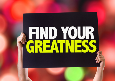 greatness: Hands holding blackboard with Find Your Greatness on bokeh background