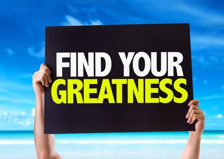 greatness: Hands holding blackboard with Find Your Greatness on beach background