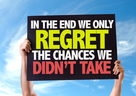 regret: Hands holding blackboard with In The End We Only Regret The Chances We Didnt Take on sky background