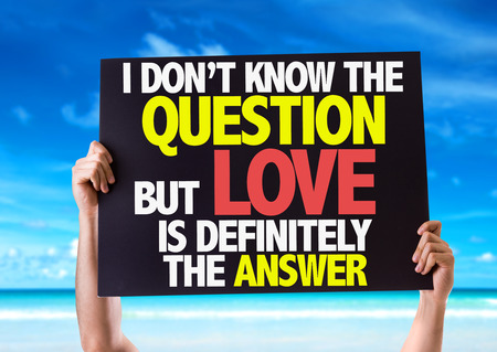 i dont know: Hands holding blackboard with I Dont Know The Question But Love Is Definitely The Answer on beach background