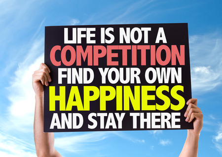 Hands holding blackboard with Life is Not A Competition, Find Your Own Happiness And Stay There on sky background