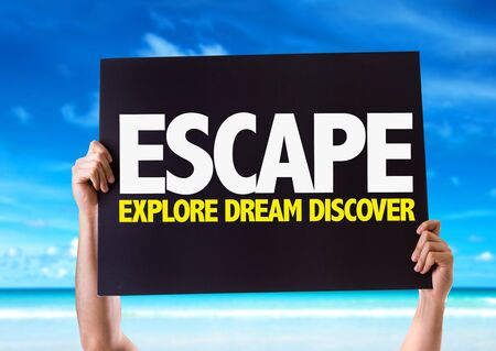 tripping: Hands holding blackboard with Escape Explore Dream Discover on beach background
