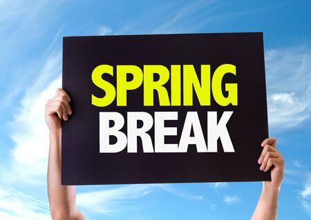 springbreak: Hands holding blackboard with Spring Break on sky background Stock Photo