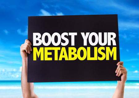 boost: Hands holding blackboard with boost your metabolism on beach background Stock Photo