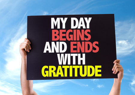 begins: Hands holding blackboard with My Day Begins And Ends With Gratitude on sky background