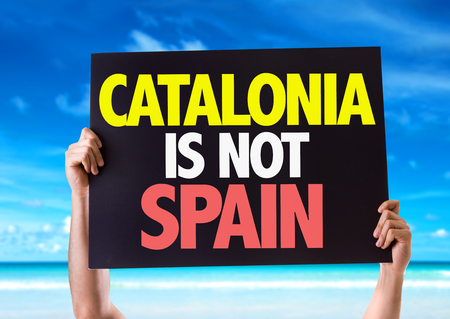 seperation: Hands holding blackboard with Catalonia Is Not Spain on beach background