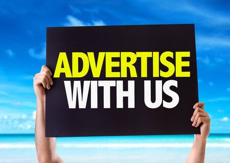 advertise: Hands holding blackboard with Advertise With Us on beach background