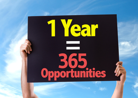 equals: Hands holding blackboard with One Year Equals 365 Opportunities on sky background Stock Photo