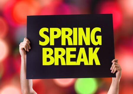 springbreak: Hands holding blackboard with Spring Break on bokeh background