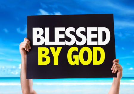 Hands holding blackboard with Blessed By God on beach background Stock Photo