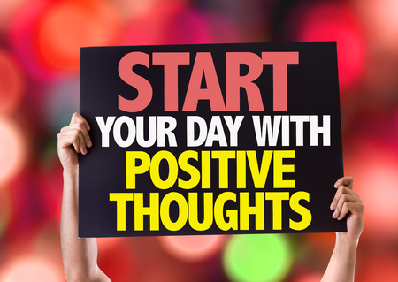 positiveness: Hands holding Start your Day with Positive Thoughts card on bokeh background