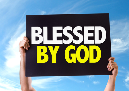 spiritual bless: Hands holding blackboard with Blessed By God on sky background Stock Photo