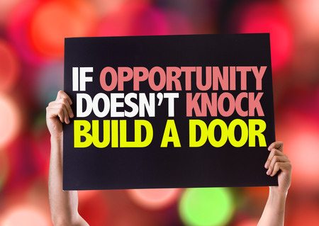 tocar la puerta: Manos que sostienen la tarjeta con el texto Si la oportunidad no llama a construir una puerta en el fondo del bokeh Foto de archivo