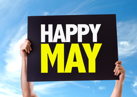 may: Hands holding card with text Happy May on sky background