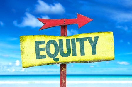 equity: Poste indicador con la equidad de texto en el fondo de playa Foto de archivo