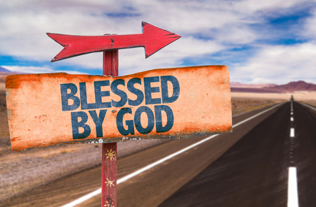 Signpost with the text Blessed by God on road background Stock Photo