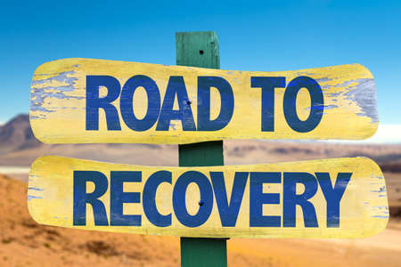 road to recovery: Signpost with the text Road to recovery on desert background