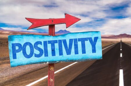 positive: Signpost with the text Positivity on road background