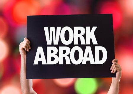 abroad: Hands holding blackboard with Work Abroad on bokeh background Stock Photo