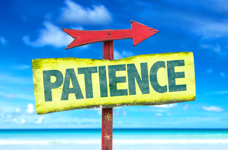 Patience sign with arrow on a beach background