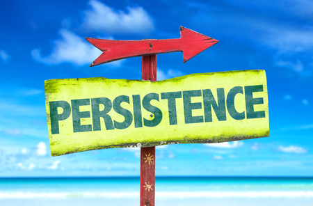 resolved: Persistence sign with arrow on beach background Stock Photo
