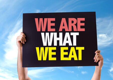 what to eat: Hands holding blackboard with We Are What We Eat on sky background