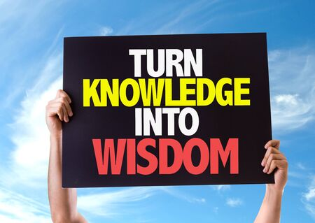 into: Hands holding blackboard with Turn Knowledge Into Wisdom on sky background