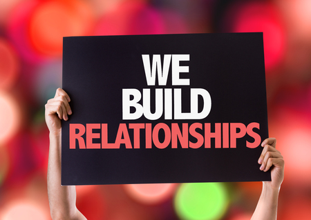 we: Hands holding blackboard with We Build Relationships on bokeh background Stock Photo
