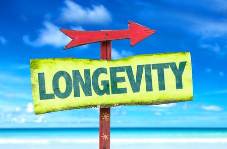 longevity: Longevity sign with arrow on beach background Stock Photo