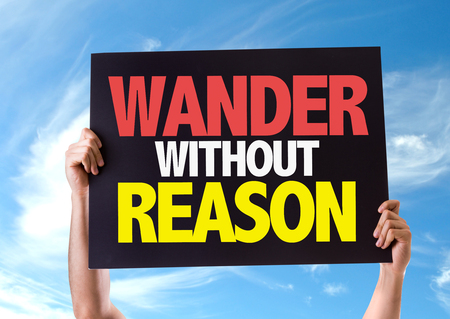 wander: Hands holding blackboard with Wander Without Reason on sky background Stock Photo