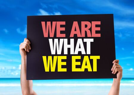 what to eat: Hands holding blackboard with We Are What We Eat on beach background