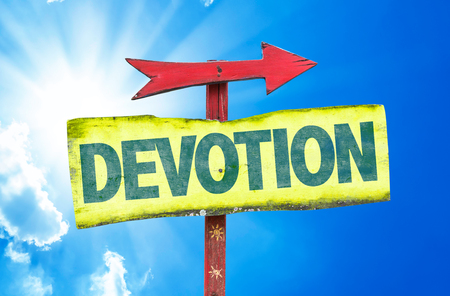 the devotion: Devotion sign with arrow on sunny background Stock Photo