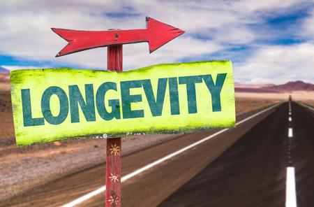 longevity: Longevity sign with arrow on a highway background Stock Photo