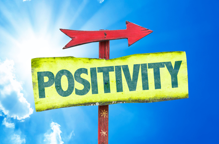positivity: Positivity sign with arrow on sunny background Stock Photo