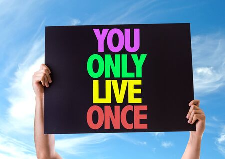 once: Hands holding blackboard with You Only Live Once on sky background Stock Photo