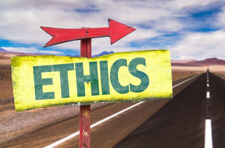 valores morales: Signpost with Ethics and arrow on a highway background Foto de archivo