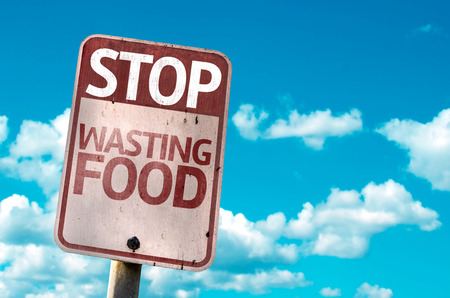 Stop Wasting Food sign with clouds and sky background