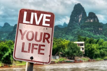 fulfilled: Live Your Life written on the road sign with village in valley background Stock Photo