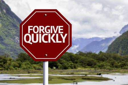 to forgive: Perdonamos escrita r�pidamente en la se�al de tr�fico con el fondo del valle Foto de archivo