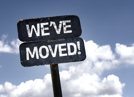 Weve Moved sign with clouds and sky background