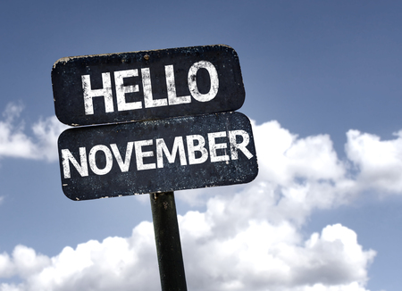november: Hello November sign with clouds and sky background