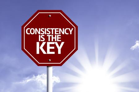 La consistencia es la clave escrita en la señal de tráfico Foto de archivo