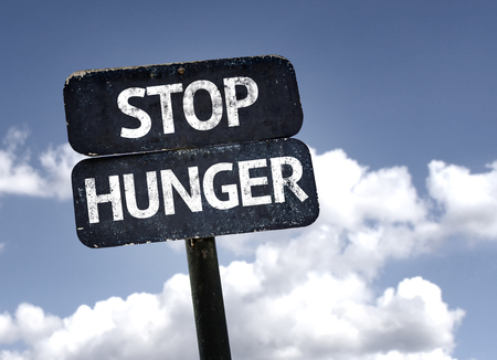 starving: Stop Hunger sign with clouds and sky background Stock Photo